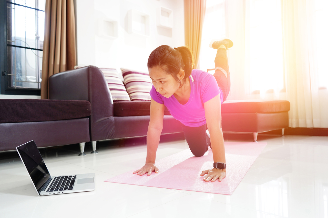 A woman exercising in her living room