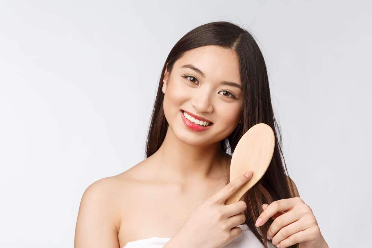 A beautiful Asian woman brushing her healthy hair