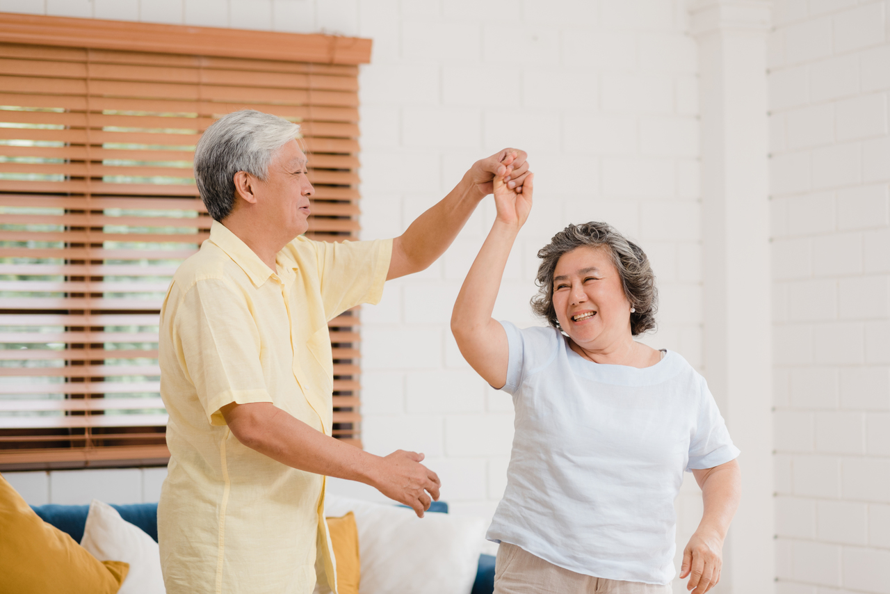 An elderly couple dancing in the living room