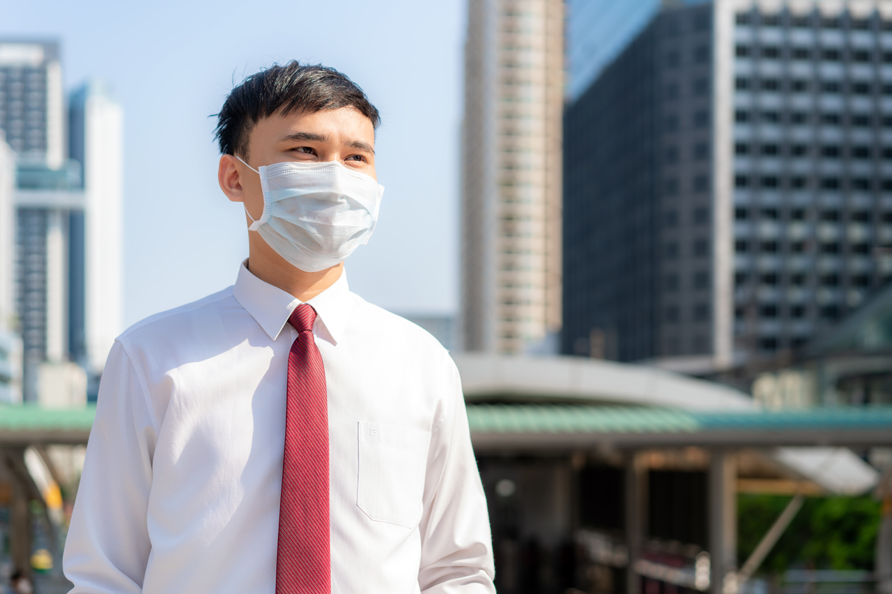 An Asian businessman going to work with a face mask