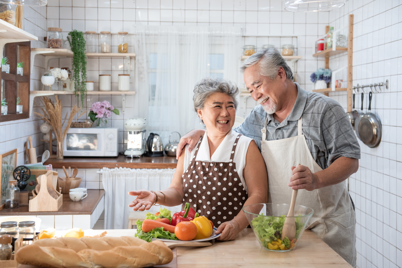 An older Asian couple making breakfast together