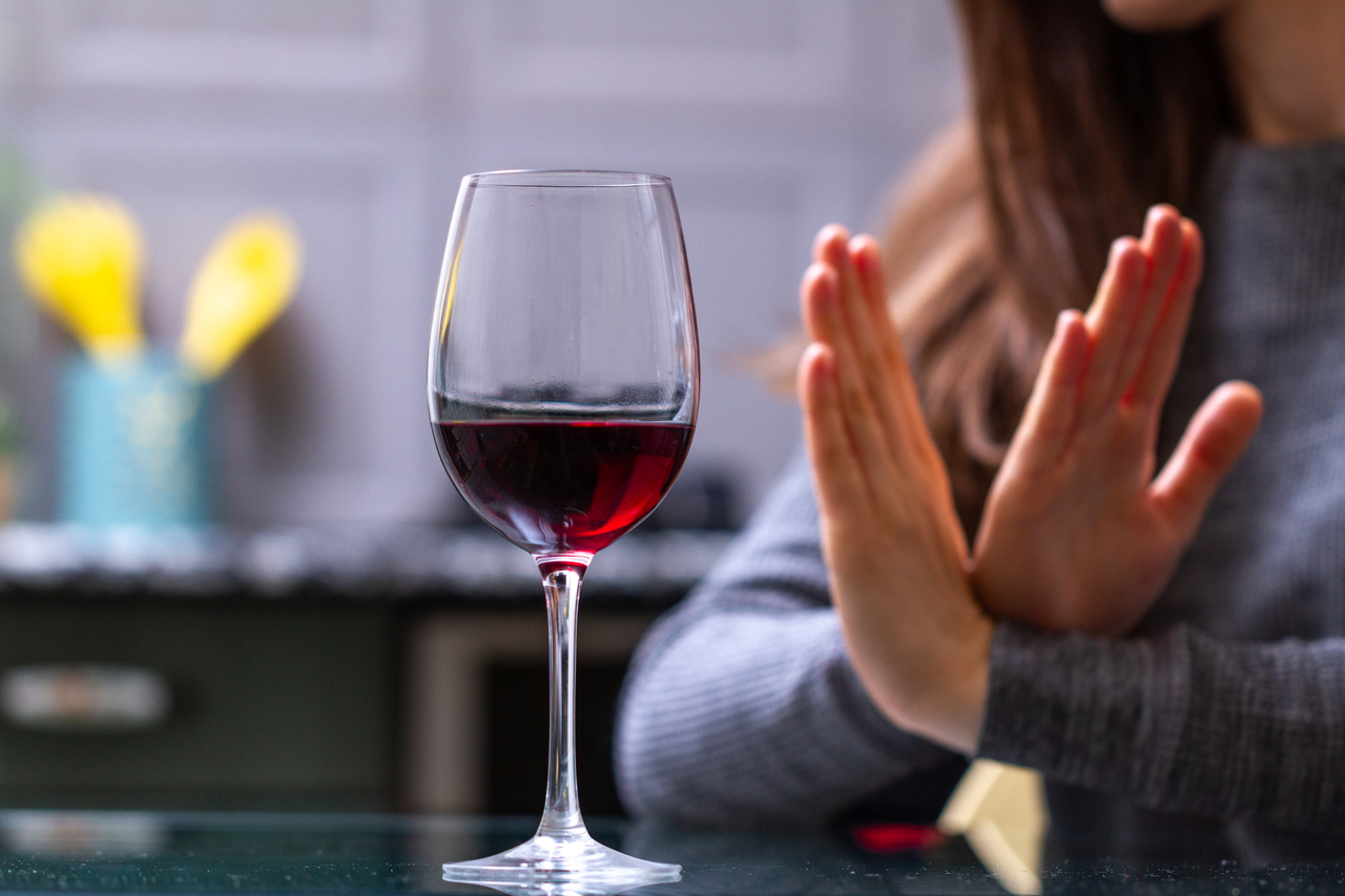 A woman refusing a glass of wine