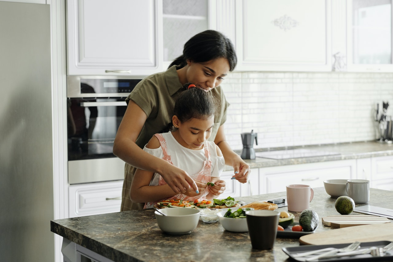A mom preparing a nutritious meal with her daughter