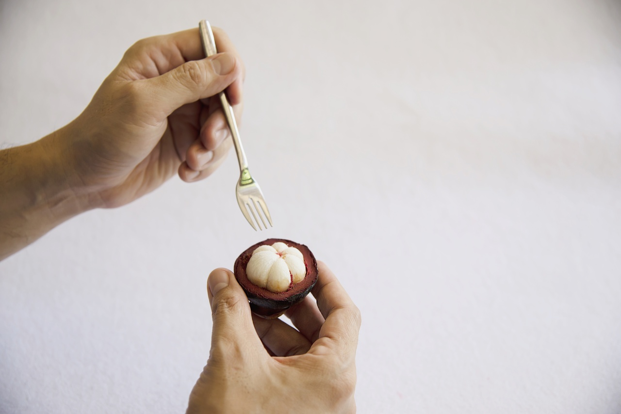 A person eating mangosteen